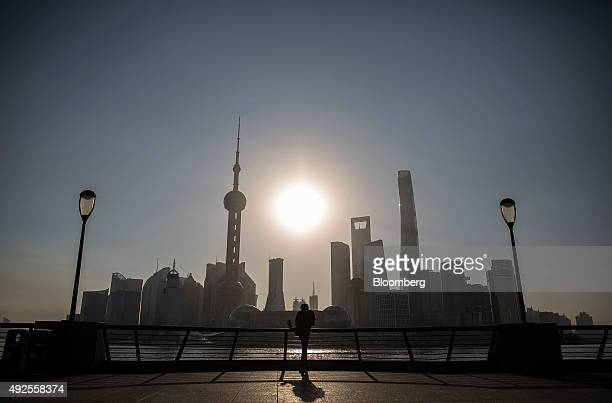 A man performs stretching exercises on the Bund while buildings of Pudong's Lujiazui financial district stand across the Huangpu River as the sun...