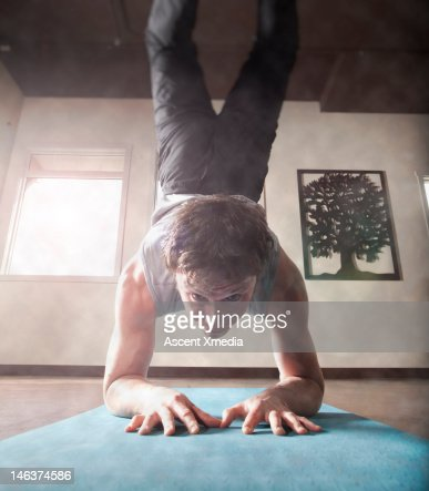 Man performs yoga handstand, in youga lounge : Stock Photo