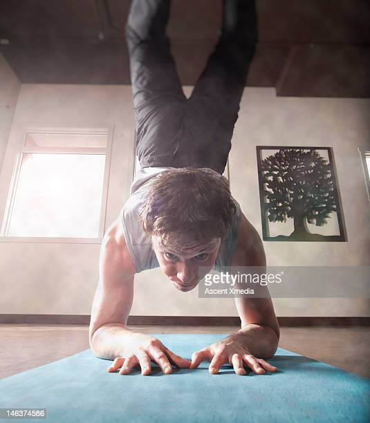 Man performs yoga handstand, in youga lounge