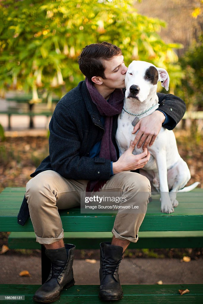 Man petting dog on park bench : Stock Photo