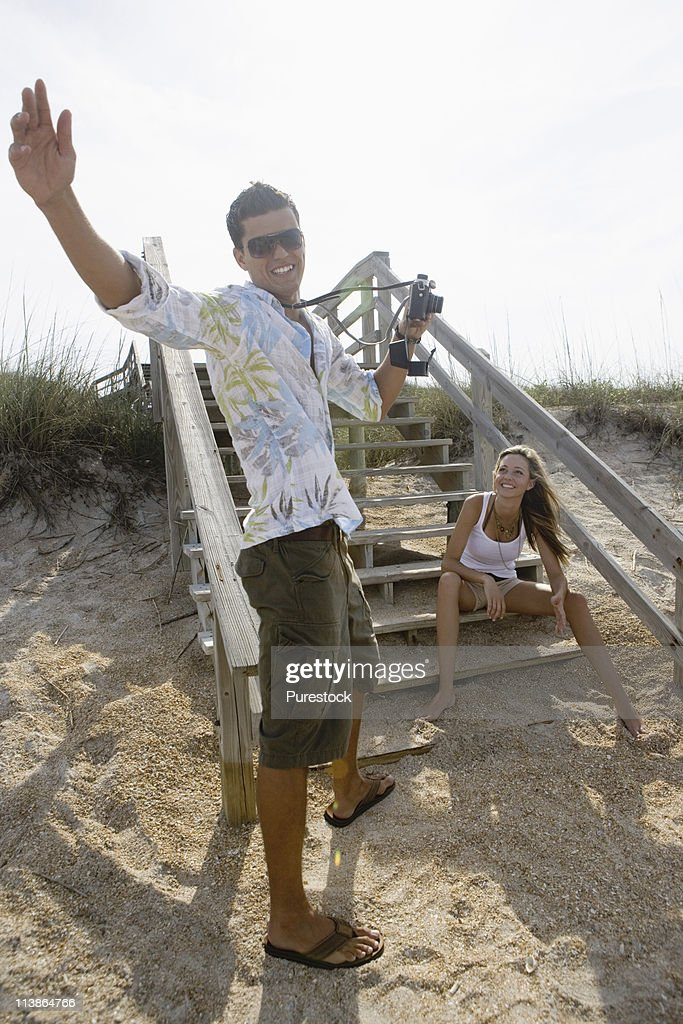 Man photographing a woman at the beach : Stock Photo