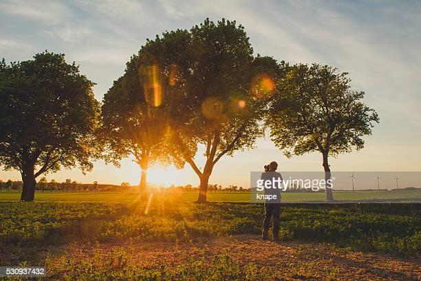 Homem fotografando ao pôr do sol em natureza