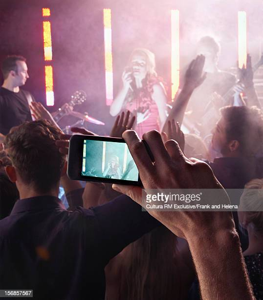 Man photographing band in club