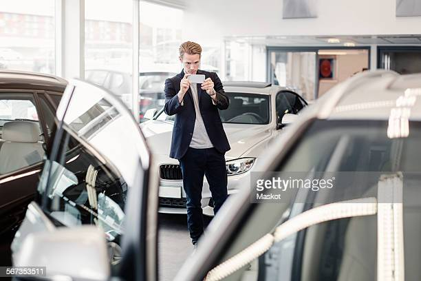 Man photographing car through smart phone at dealership store