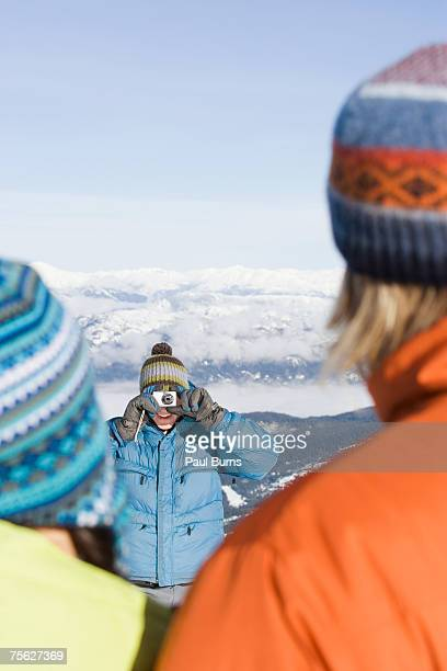 Man photographing couple in mountain landscape in winter, view from behind couple