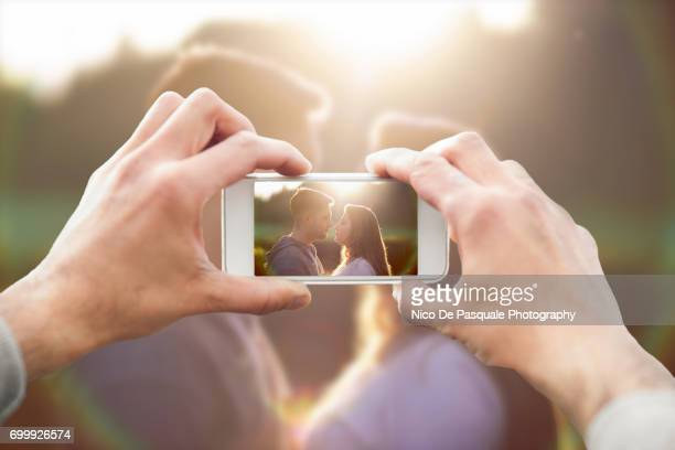 Man photographing couple kissing