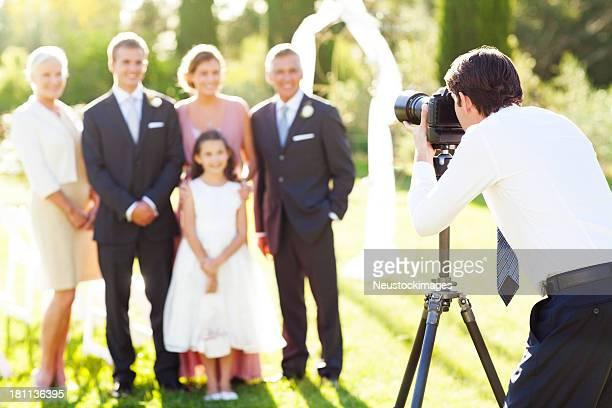 Uomo fotografare famiglia al matrimonio all'aperto