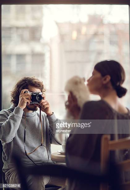 Man photographing his girlfriend with dog in a cafe.