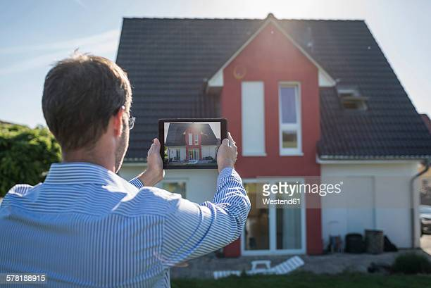 Man photographing his house with digital tablet