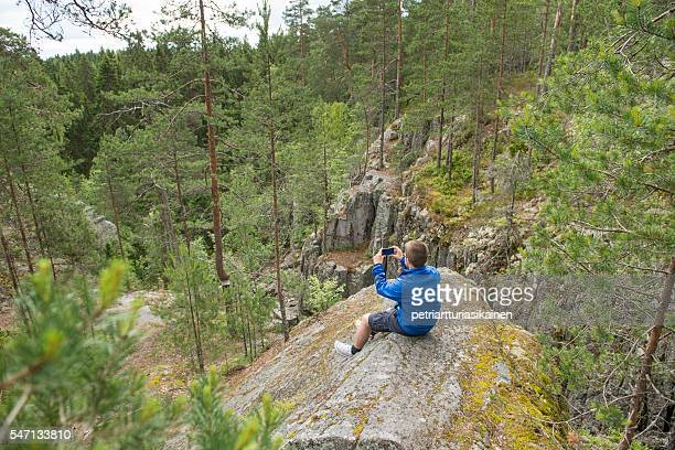Man photographing in forest with mobile phone.