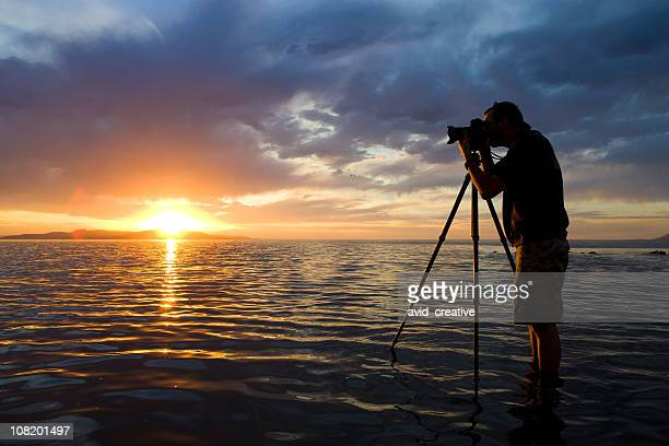 Man Photographing in Water at Sunset