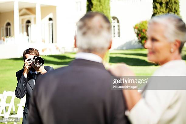 Man Photographing Mature Couple At Garden Wedding