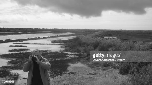 Man Photographing On Field By River