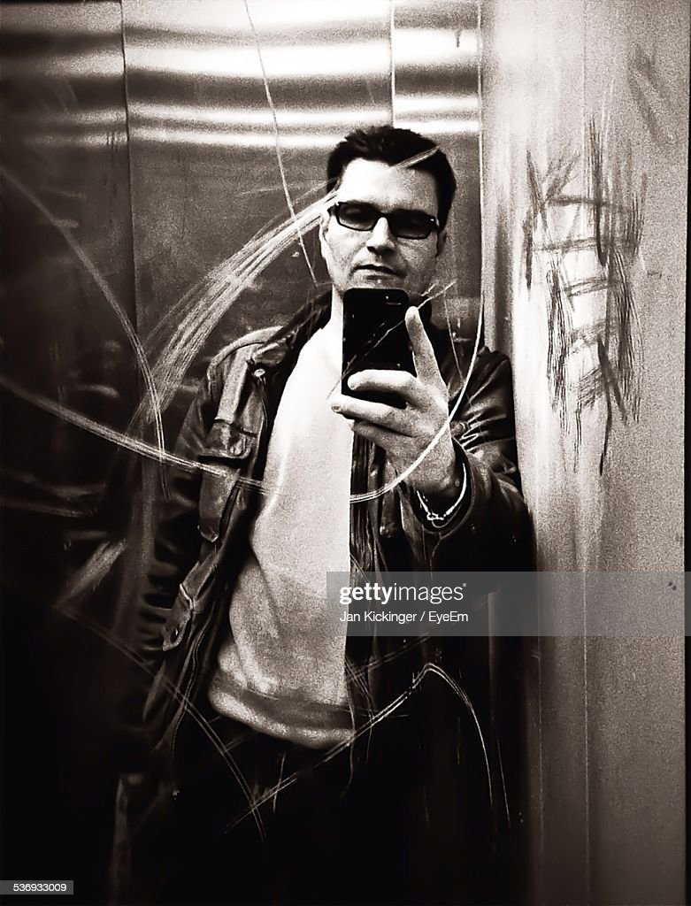 Man Photographing Reflection In Scratched Elevator Mirror