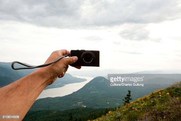 Man photographing self in rural scene