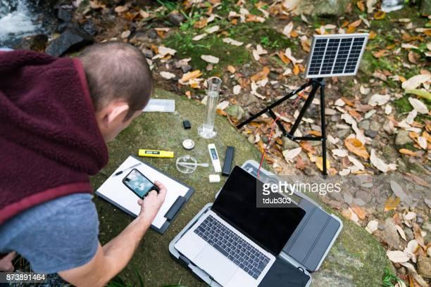 Een man die fotograferen sommige watermonsters in een externe zonne-aangedreven onderzoeksstation