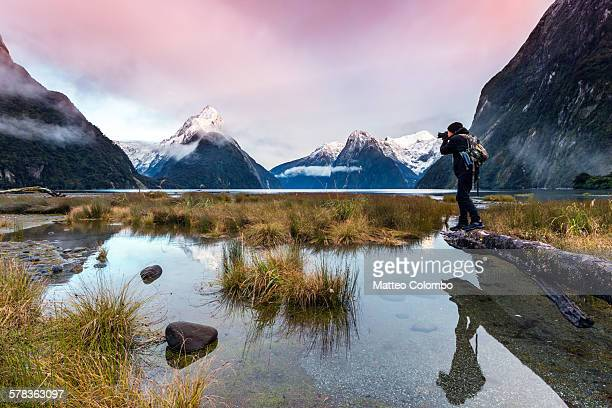 Man photographing sunset at Milford Sound