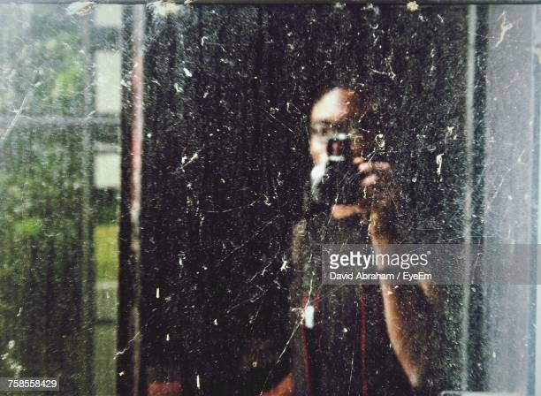 Man Photographing Through Camera Reflecting On Glass