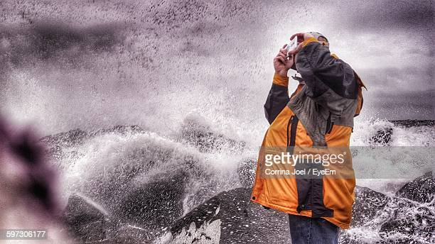 Man Photographing Through Smart Phone Against Wave Splashing On Shore Against Sky