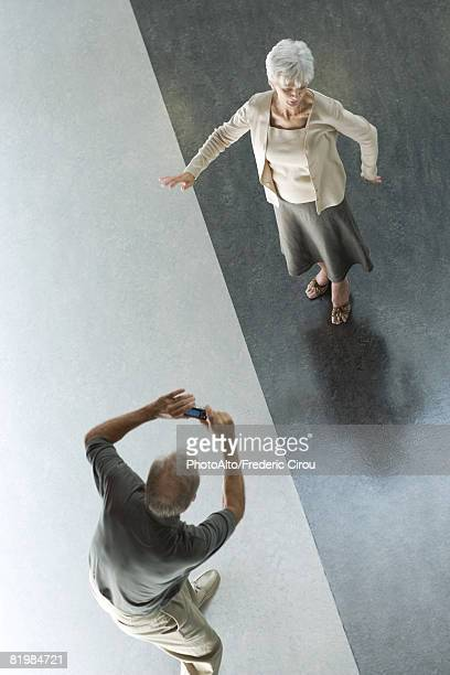 Man photographing wife with digital camera, viewed from directly above