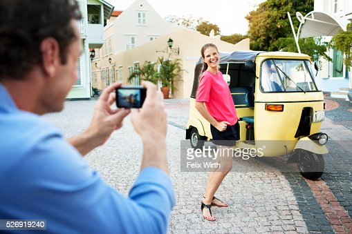 Man photographing woman in front of tuk tuk : ストックフォト