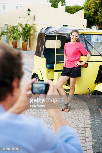 Man photographing woman in front of tuk tuk : Stock-Foto