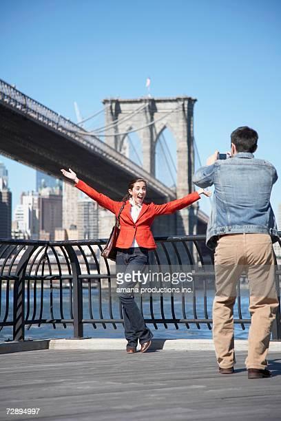 Man photographing woman near Brooklyn Bridge, New York City, New York, USA