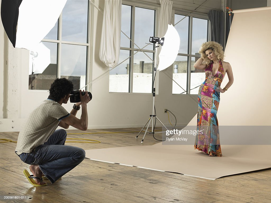 Man photographing young female model on set in photo studio : Stock Photo