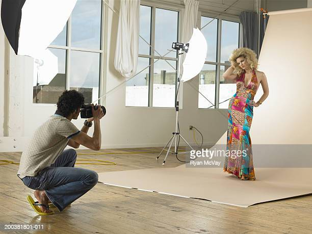 Man photographing young female model on set in photo studio