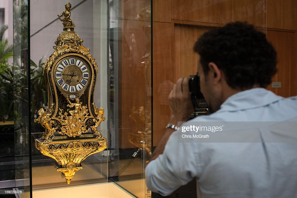 A man photographs a 1730 Boulle Marquetry Cartel clock on display January 9, 2013 at Marina Bay Sands in Singapore. To commemorate the Year of The Dragon,the exhibition 'The Final 100 Days of the Year of the Dragon' showcases a selection of rare 18th century French 'Chinoiserie' furniture and ornaments from the Kraemer gallery collection in Paris. The Kraemer Gallery boasts the worlds largest privately-owned collection of French 18th century furniture and ornaments considered museum quality. The exhibition is on display until Chinese New Year on 10 February 2013.
