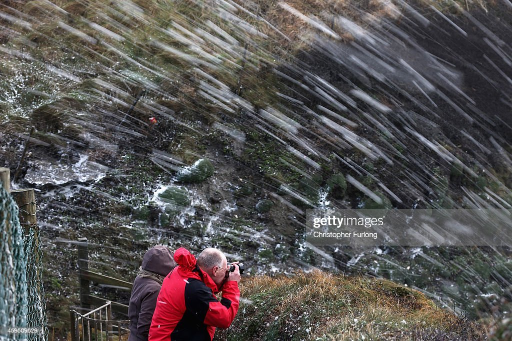 A man photographs a blizzard of sea foam whipped up by the wind near Trearddur Bay on December 27, 2013 in Anglesey, United Kingdom. A yellow 'be aware' warning has been issued for many parts of Britain as the country is affected by gale force winds and heavy rain.