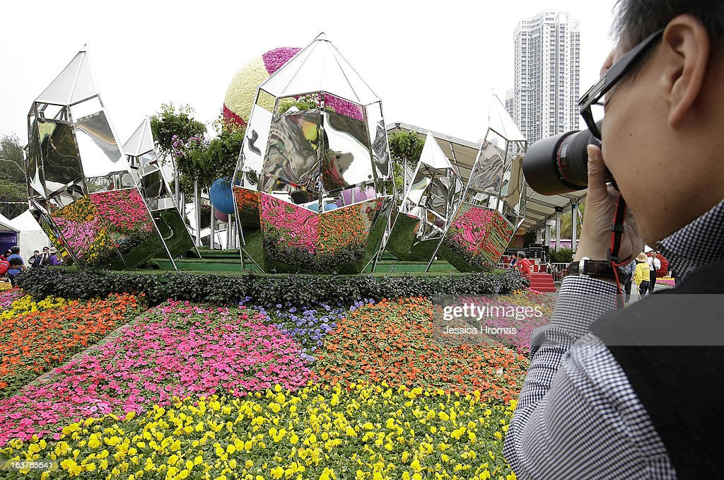 A man photographs a display of flowers which includes mirrored sculptures at the 2013 Hong Kong Flower Show at Victoria Park on March 15, 2013 in Hong Kong, Hong Kong. The 2013 Hong Kong Flower Show opened today and will continue until March 24, 2013.