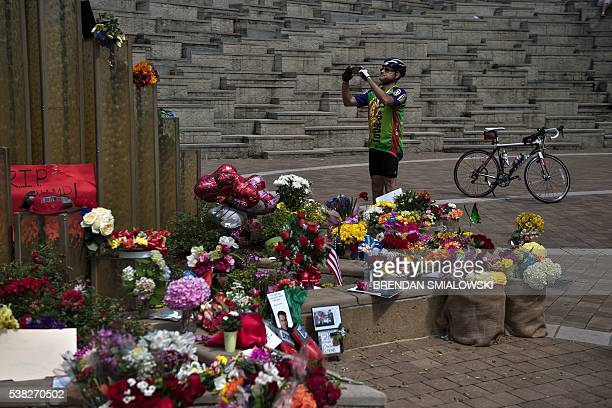A man photographs a memorial as he pays his respects to boxing legend Muhammad Ali at the Muhammad Ali Center June 5 2016 in Louisville Kentucky The...