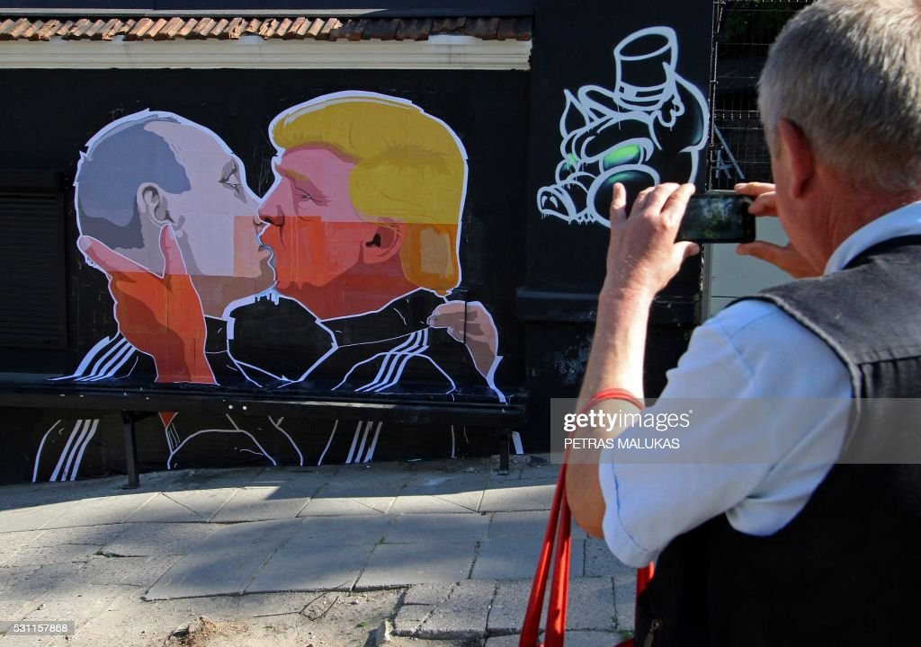 A man photographs a mural on a restaurant wall depicting US Presidential hopeful Donald Trump and Russian President Vladimir Putin greeting each...
