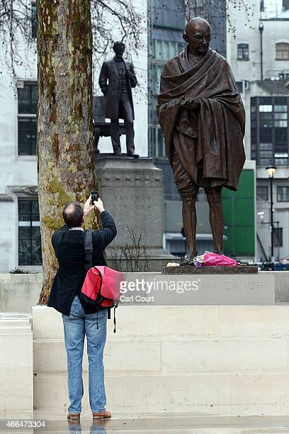 A man photographs a statue of Indian independence leader Mahatma Gandhi in Parliament Square on March 16 2015 in London England The 27m bronze statue...