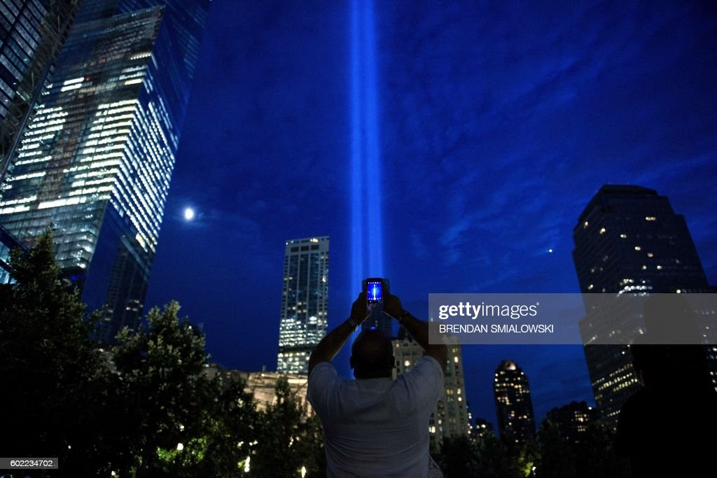 TOPSHOT - A man photographs beams of light symbolizing the two World Trade Center towers the night before the 15th anniversary of the September 11, 2001 terrorist attacks in the United States on September 10, 2016 in New York, New York. / AFP / Brendan Smialowski