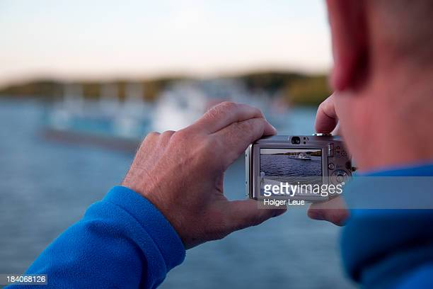 Man photographs freighter with compact camera