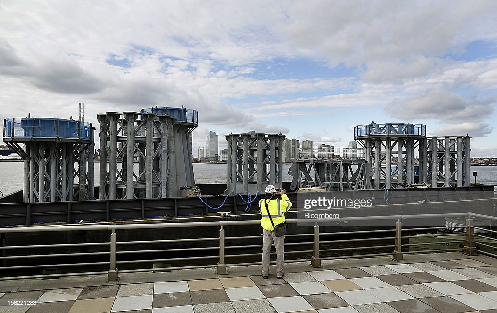A man photographs the barge delivering the spire of One World Trade Center in New York, U.S., on Tuesday, Dec. 11, 2012. The crowning spire, split into nine pieces weighing 70 tons each, was brought across New York Harbor from New Jersey's Port Newark today. Photographer: Victor J. Blue/Bloomberg via Getty Images