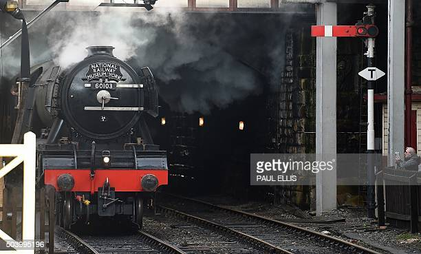 A man photographs The Flying Scotsman as it arrives at Bury Bolton Street rail station in Bury north west England on January 8 on the East Lancashire...