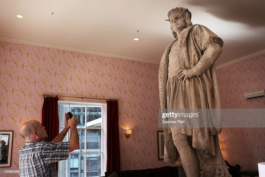 A man photographs the iconic 13-foot statue of Christopher Columbus is viewed from the 810-square-foot 'living room' art installation by Japanese artist Tatzu Nishi on September 19, 2012 in New York City. Viewed as a piece of conceptual art, 'Living Room', which sits 70-feet above ground level and is only accessible via a scaffold-encased staircase, has been temporarily built around the Columbus Monument in Columbus Circle. Beginning Thursday, up to 25 people at a time can enter the living room to view up close the 1892 marble figure of the Italian explorer.