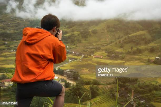 A man photographs the landscape. Rice terraces in the Vietnam. Rice cultivation in the Sapa. Traveling concept.