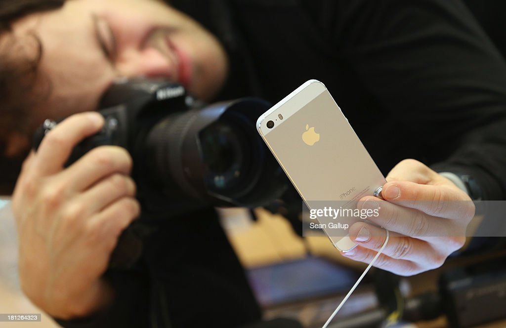 A man photographs the new Apple iPhone 5S smartphone at the Berlin Apple Store on the first day of sales on September 20, 2013 in Berlin, Germany. The new iPhone 5S and 5C phones went on sale all over the world today and hundreds of customers waited outside the Berlin store in the rain to be among the first to buy the new phones starting at 8am.