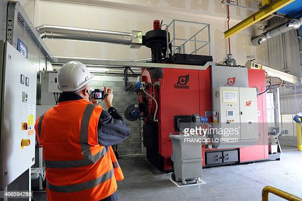 A man photographs the new industrialstrength biomass boiler installed at the Onnaing Toyota factory in the north of France on March 17 2015 AFP PHOTO...