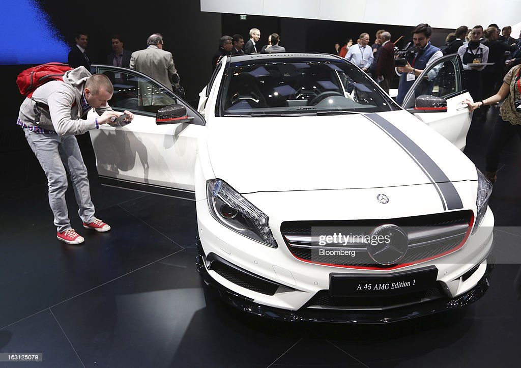 A man photographs the new Mercedes-Benz A 45 AMG automobile, produced by Daimler AG, on the first day of the 83rd Geneva International Motor Show in Geneva, Switzerland, on Tuesday, March 5, 2013. This year's show opens to the public on Mar. 7, and is set to feature more than 100 product premiers from the world's automobile manufacturers. Photographer: Chris Ratcliffe/Bloomberg via Getty Images