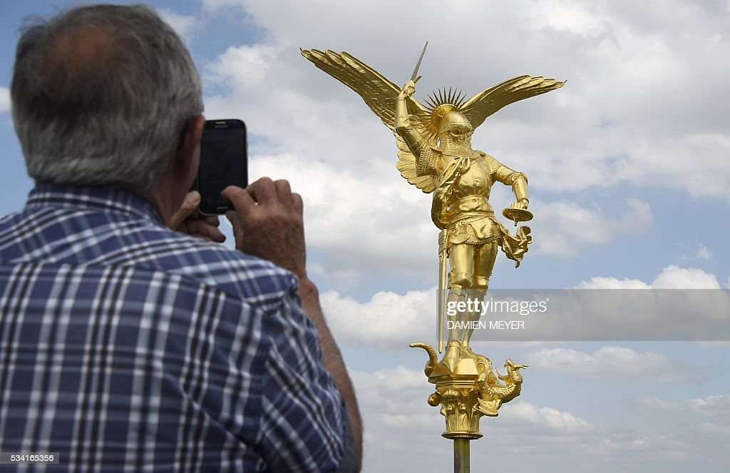 A man photographs the statue of the Archangel Michael, regilded and restored with a new lighting rod, on the eve of its placement back atop the Mont Saint-Michel Abbey on May 25, 2016 in Mont Saint-Michel. / AFP / DAMIEN