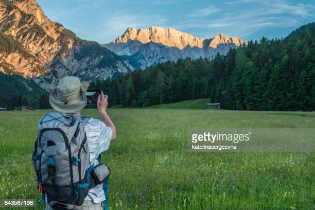 man photographs the sunset over the mountains
