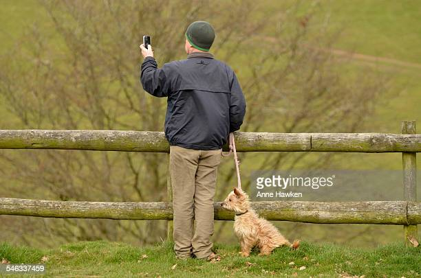 A man photographs the view with a mobile device whilst out walking his dog