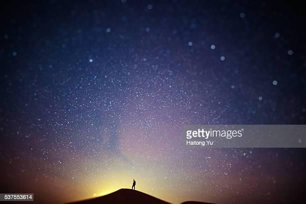 Man picking star on top of sand dune