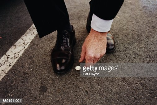 Man picking up coin from street : Stock Photo