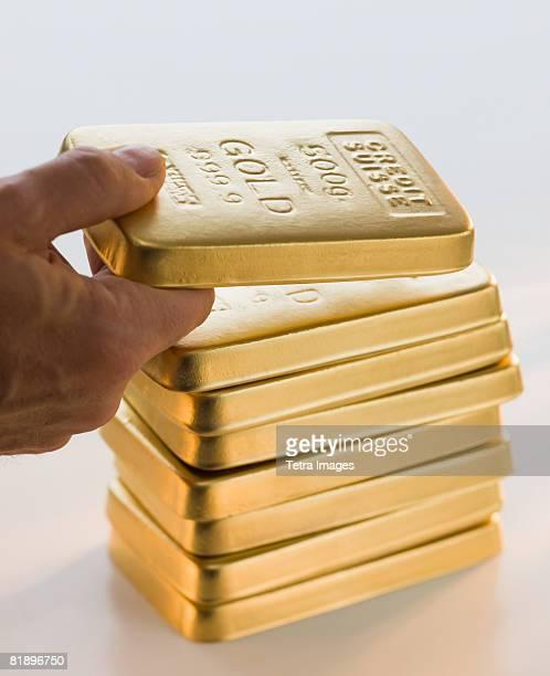 Man picking up gold bar